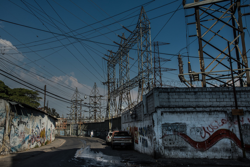 "CARACAS, VENEZUELA -MARCH 22, 2016: Residents of  Catia, a slum in Caracas that is regularly subject to state-mandated electricity rationing, walk past an electrical substation run by Corpoelec, the state power corporation of Venezuela.  Venezuela is shutting down this week, as the government struggles with a deepening electricity crisis.  President Nicolas Maduro gave everyone an extra three days off work, extending the two-day Easter holiday, according to a statement in the Official Gazette published late last Tuesday.  The government has rationed electricity and water supplies across the country for months and urged citizens to avoid waste as Venezuela endures a prolonged drought that has slashed output at hydroelectric dams. The ruling socialists have blamed the shortage on the El Nino weather phenomena and ""sabotage"" by their political foes, while critics cite a lack of maintenance and poor planning.  PHOTO: Meridith Kohut"