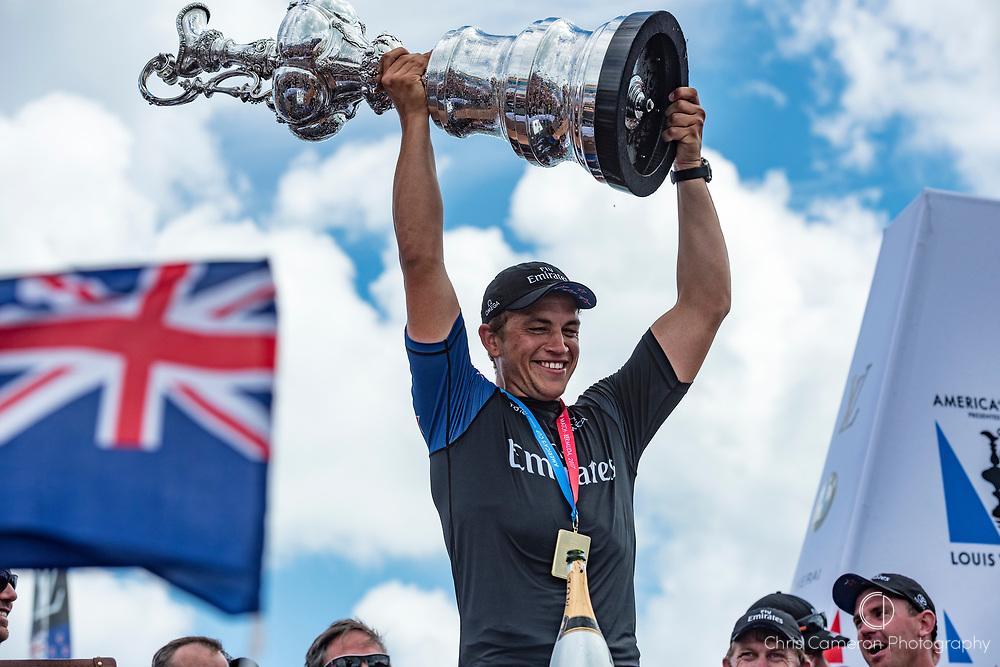 The America's Cup Village, Bermuda, 26th June 2017. Emirates Team New Zealand Sailor / Cyclist Andy Maloney with the America's Cup.