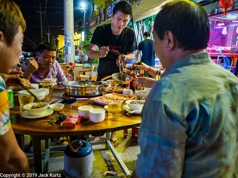 """14 FEBRUARY 2019 - SIHANOUKVILLE, CAMBODIA:  Chinese businessmen have dinner at a streetside Chinese hotpot restaurant. There are thousands of Chinese workers in Sihanoukville who work to support the casino and hotel industry in the town and thousands of other Chinese migrants have moved into Sihanoukville and opened businesses that cater to the workers. There are about 80 Chinese casinos and resort hotels open in Sihanoukville and dozens more under construction. The casinos are changing the city, once a sleepy port on Southeast Asia's """"backpacker trail"""" into a booming city. The change is coming with a cost though. Many Cambodian residents of Sihanoukville  have lost their homes to make way for the casinos and the jobs are going to Chinese workers, brought in to build casinos and work in the casinos.     PHOTO BY JACK KURTZ"""