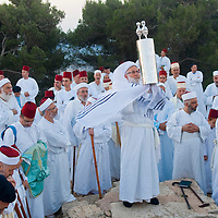 NABLUS, WEST BANK - JUNE 24 : A priest of the ancient Samaritan community holds up a Torah scroll during the holy day of Shavuot in Mount Gerizim on June 24 2012, Shavuot is an holyday commemoretas the anniversary of the day god have given the Torah to the Israelites