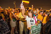 "23 JUNE 2012 - PHOENIX, AZ:  A Unitarian woman carrying an electric candle marches the Maricopa County Jail in Phoenix Saturday. About 2,000 members of the Unitarian Universalist Church, in Phoenix for their national convention, picketed the entrances to the Maricopa County Jail and ""Tent City"" Saturday night. They were opposed to the treatment of prisoners in the jail, many of whom are not convicted and are awaiting trial, and Maricopa County Sheriff Joe Arpaio's stand on illegal immigration. The protesters carried candles and sang hymns.     PHOTO BY JACK KURTZ"