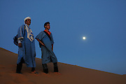 Two young, good tempered men are standing on a dune in a sand desert with the horizon, the blue sky and the full moon in the background. Merzouga. Morocco. Africa.