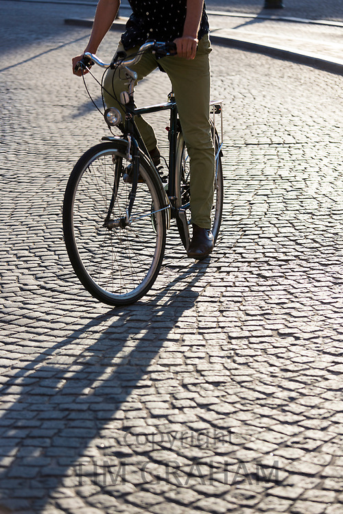 Male cyclist cycling one of the old-fashioned bicycles on cobblestones in Bruges, Belgium