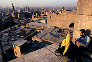 A courting couple sit in conversation on ramparts of the Citadel, overlooking Old Cairo and the Sultan Hassan Mosque.