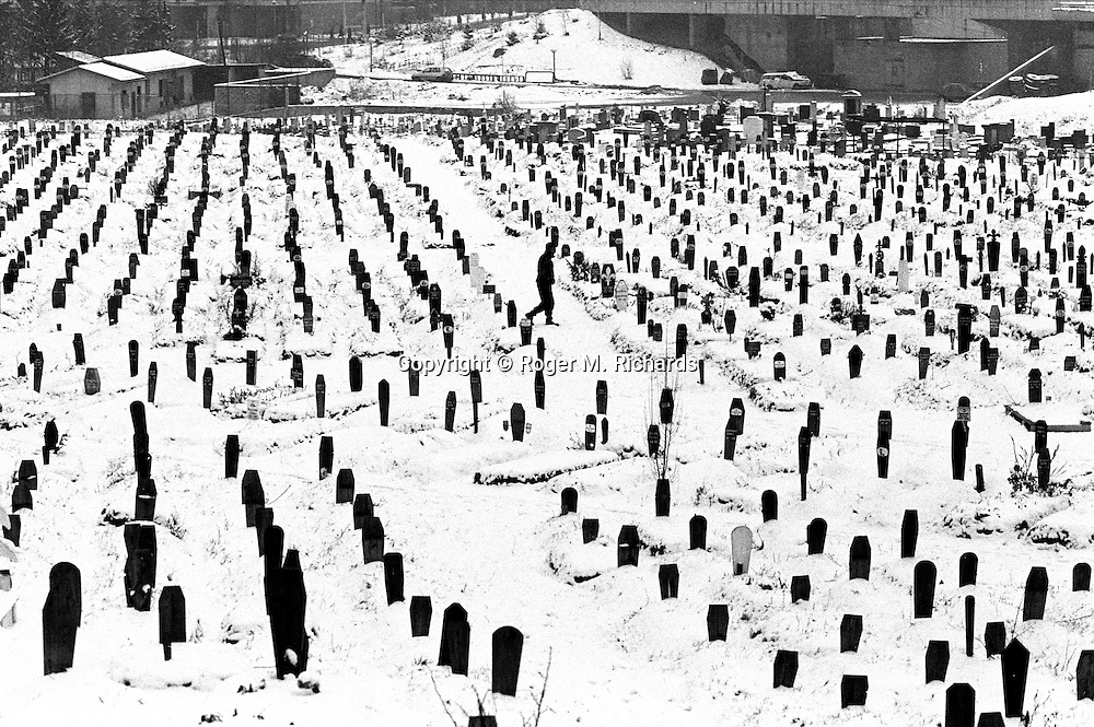 A Bosnian soldier walks through the Kosevo soccer field that was turned into a cemetery, during the final days of the siege of the city, Sarajevo, Bosnia and Herzegovina, February 1996. PHOTO BY ROGER RICHARDS