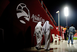 Local Qatar men in the stadium beside Asian Cup signage