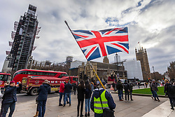 © Licensed to London News Pictures. 14/01/2019. London UK. A yellow vest protester waves a union jack outside the Houses of Parliament in Parliament square today.Photo credit: Andrew McCaren/LNP