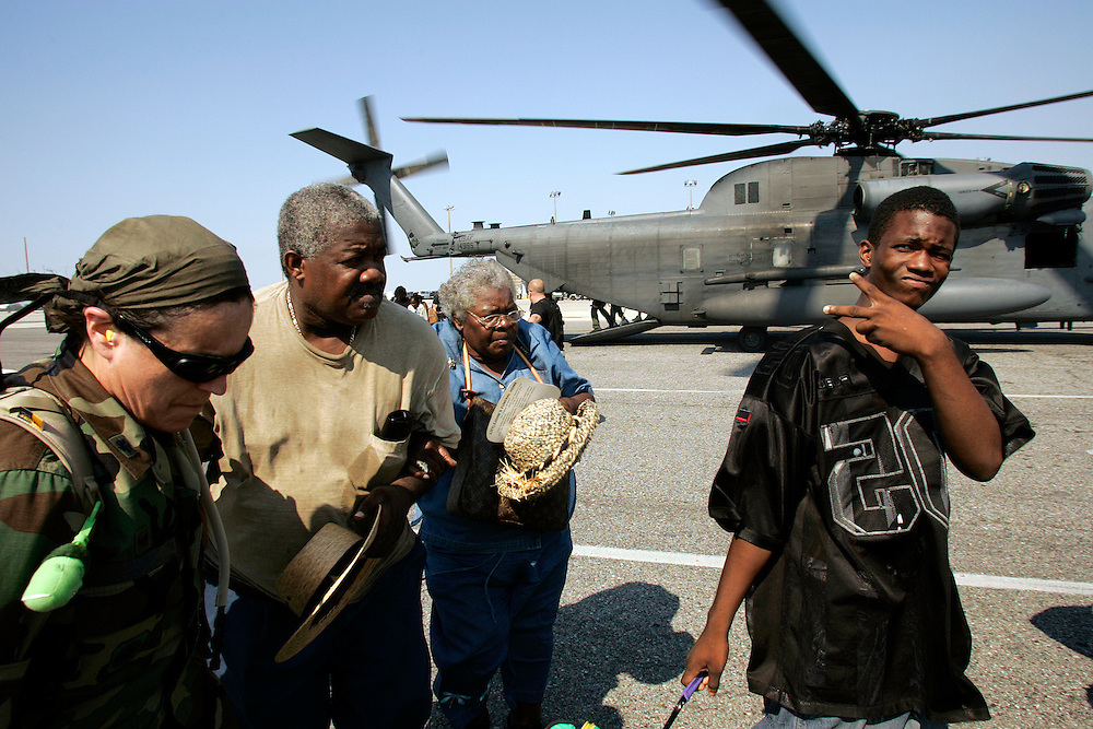 NEW ORLEANS, LA - September 4, 2005:  Evacuees from New Orleans, Louisiana were being flown to the city's airport via helicopter and unloaded on the tarmac on September 4, 2005. In a scene similar to that of a war zone evacuation, they were then hustled from the helicopter onto waiting cargo carts ( normally used to move luggage) and rushed into the airport where they received medical attention. Shortly after entering the airport, evacuees were screened and divided into groups and told to go to a certain boarding gate. Evacuees only find out the destination of the flight, and their new temporary home, after boarding the flight. (Photo by Todd Bigelow/Aurora)..