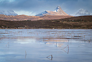 Sunset illuminates Stac Pollaidh over an ice covered Loch a'Choarainn near Achnahaird in Scotland.