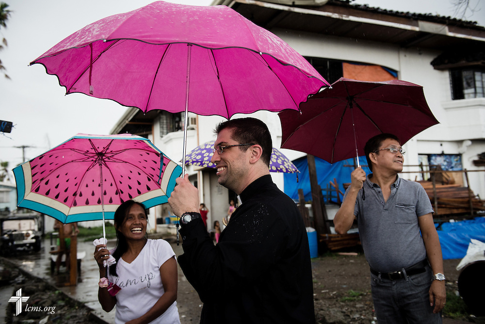 The Rev. Ross Johnson, director of LCMS Disaster Response, uses an umbrella as rain pours down on reconstruction efforts leftover from Typhoon Haiyan in Tacloban, Leyte Province, Philippines, on Friday, March 14, 2014. LCMS Communications/Erik M. Lunsford