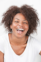 Portrait of a joyful African American young woman laughing against white background