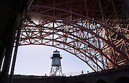 The lighthouse on the ramparts of Fort Point, is framed by the arch of the Golden Gate Bridge