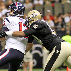 August 25, 2012; New Orleans, LA, USA; Houston Texans quarterback T.J. Yates (13) fumbles as he is hit by New Orleans Saints defensive end Turk McBride (90) during the second half of a preseason game at the Mercedes-Benz Superdome. The Saints defeated the Texans 34-27.  Mandatory Credit: Derick E. Hingle-US PRESSWIRE