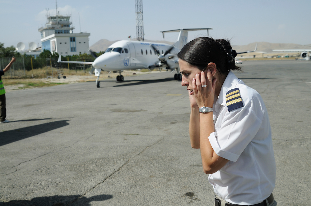 "Pilot, Danielle Aitchison, covers her ears while an UNHAS Beechcraft 1900D taxis at Kabul International Airport.  Danielle flies in Afghanistan for The United Nations Humanitarian Air Service (UNHAS).   .. ...When asked about flying in a war zone, she says,  ""I'm just a normal average female.  My job is maybe a little different to some, but I have the same feminine side as other women.  I don't have any trouble going back to New Zealand relating to people.  I'm just a regular chick.""."