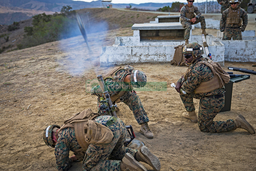 U.S. Marine Corps Sgts. Benny Carithers (bottom), Heroshi Mendoza (center), and Khwame Johnson, combat instructors, Weapons Platoon, A Company, Infantry Training Battalion, School of Infantry-West, give a live-fire demonstration during the Basic Mortarman Course at Range Mortar Position 6, Marine Corps Base Camp Pendleton, California, Oct. 4, 2018. The students were evaluated on the use and employment of the 60mm M224 mortar system. They must successfully qualify before moving on to the M252 81mm mortar system. (U.S. Marine Corps photo by Cpl. Dylan Chagnon)