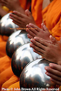 Novice Buddhist monks are gathered with their bowls to pay a birthday tribute to King Rama IX of Thailand near Tha Pae Gate in Chiang Mai, Thailand. This religious ceremony takes place annually and is marked by hundreds of monks with clasped hands performing a prayer like gesture.