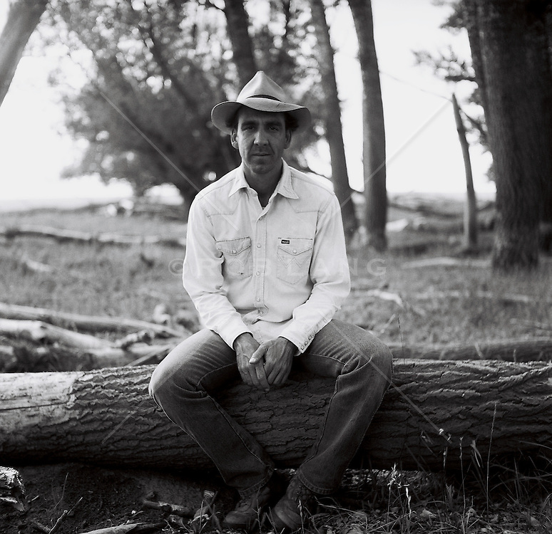 Man sitting on a fallen tree trunk in New Mexico