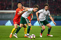 Harry Wilson, center, of Wales national football team kicks the ball to make a pass against Wei Shihao of Chinese national men's football team in the semi-final match during the 2018 Gree China Cup International Football Championship in Nanning city, south China's Guangxi Zhuang Autonomous Region, 22 March 2018.