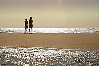 A couple standing on the beach and lokking out to the sparkling reflexes of a late afternoon sun setting to the Atlantic Ocean. My Keywords would be 'hope' or 'Future' od 'Determination' Landscape, Seascape