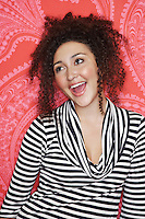 Teenage Girl in stripy blouse standing in front of  Colourful Wallpaper