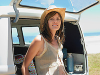 Young woman leaning on open tailgate of van half length