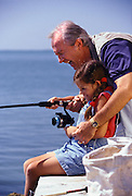 Grandfather showing granddaughter how to reel in the fish caught fishing from a pier