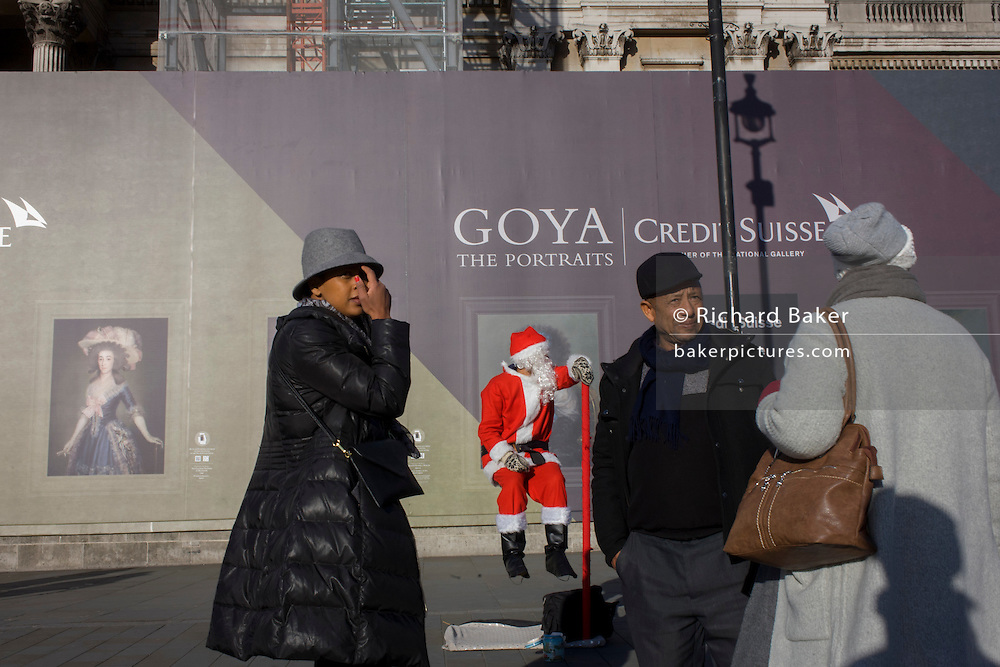 A busker dressed as Santa with visitors to Trafalgar Square, central London