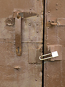 Close up of an old metal door locked with a padlock
