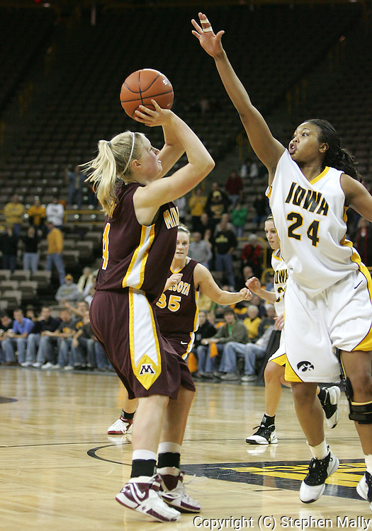 25 JANUARY 2007: Minnesota guard Emily Fox (4) puts a shot up in front of Iowa forward Jenee Graham (24) in Iowa's 80-78 overtime loss to Minnesota at Carver-Hawkeye Arena in Iowa City, Iowa on January 25, 2007.
