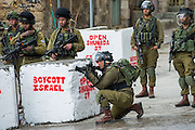 Israeli soldiers fire rubber-coated steel bullets and stun grenades at Palestinian boys throwing stones.