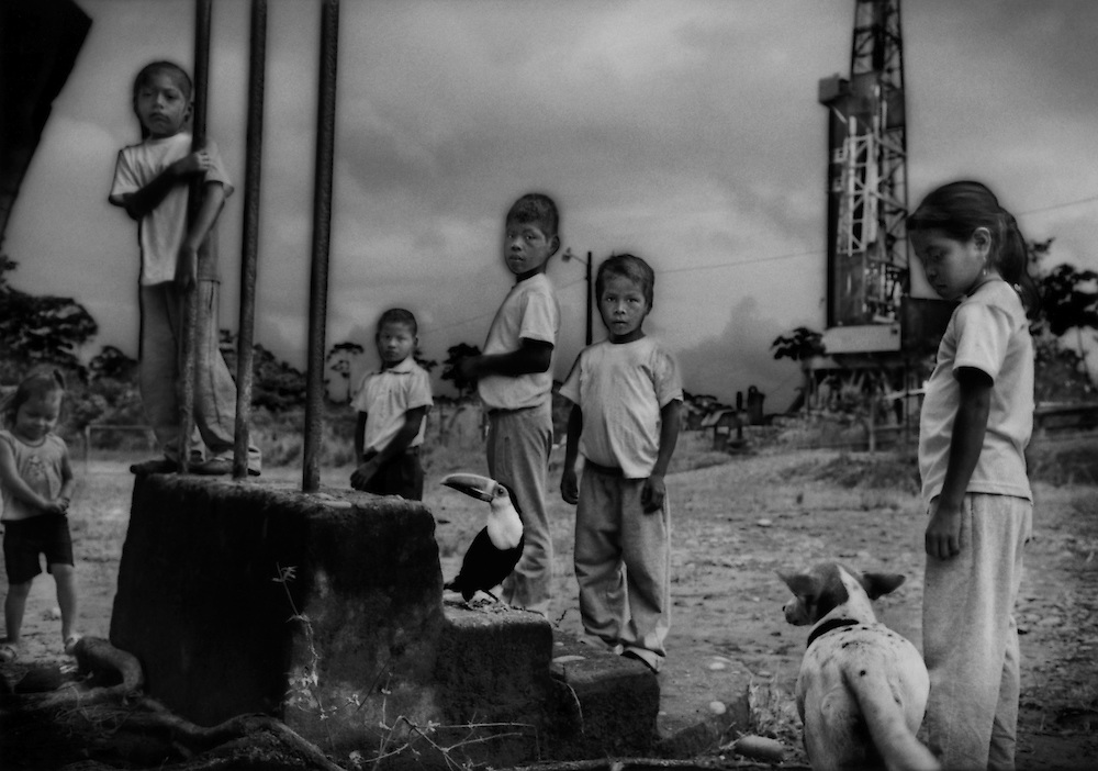 """""""Afectados"""" (Affected Ones): Oil derrick towers above students, with their pet toucan, in front of their elementary school, where they must endure the noise, noxious fumes and the dust raise by heavy trucks associated with the petroleum business.  Near Dayumi along Via Auca.  Ecuadorian Amazonas."""
