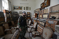 Aleppo, Syria, January 2013 -   ABU YOUSSEF, a former auto mechanic who is now a captain of a Free Syrian Army unit, is stationed in a rare, not-yet-bombed house of a resident named AHMED in the Old City section of Aleppo. AHMED has a habit of collecting antique radios and clocks, most never used.(Photo by Miguel Juárez Lugo)
