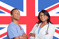 Portrait of confident mixed race male and female surgeons over British flag