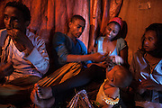 Two customers eat qat with young prostitutes, age 16 and 17 (left and right). Drug abuse is one of the consequences of sex work, both clients and prostitute use to have for long penformance.<br /> <br /> Addis Ababa, Ethiopia, 30-01-2013.<br /> <br /> To protect the identities of the recorded subjects names are omitted