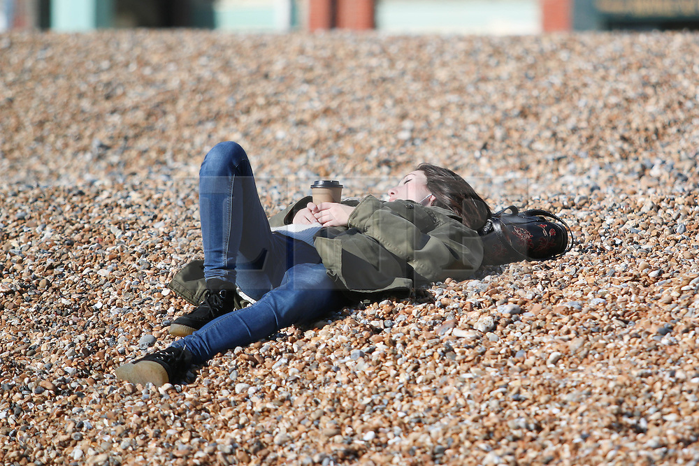 © Licensed to London News Pictures. 03/03/2015. Brighton, UK. A woman on Brighton beach relaxing in the first few sunny days of Spring 2015. Photo credit : Hugo Michiels/LNP