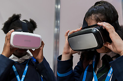 © Licensed to London News Pictures. 15/03/2016. London, UK. A pair of students try out virtual reality headsets.  Technology fans visit the Wearable Technology Show at the Excel Centre.  The largest dedicated event for connected technology, the show features innovative products from start-ups as well as products from major technology companies and includes the latest in virtual reality and augmented reality devices and software. Photo credit : Stephen Chung/LNP