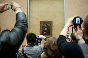 Visitors to the Louvre try to capture the Mona Lisa.