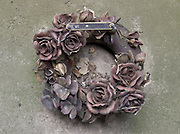 close up of a stone made flower wreath on top of a grave