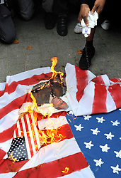 CENTRAL LONDON. British Muslim activists burn the US flag outside the American embassy in London to voice their anger at the plan by a US Christian pastor, Terry Jones,  to burn copies of the Koran on the same day. However, the US pastor has now postponed the event.  11 September 2010. STEPHEN SIMPSON.