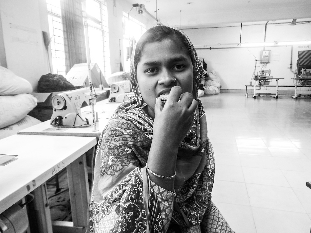 Taken by a female photographer on one of our photography programs in Bangladesh, depicting a female garment worker taking a cookie break.