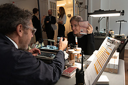 """© Licensed to London News Pictures. 05/10/2018. London, UK. American artist Tom Sachs producing a passport with his 24hliveperformanceSwiss Passport Office. The 24hliveperformanceSwiss Passport Office is on show at the Galerie Thaddaeus Ropac. Those wishing to purchase a passport will be photographed and have their name hand-typed onto a serial-numbered passport issue, stamped with a Studio endorsement and entered into the permanent database. Passports cost €20 (no British pounds will be accepted). Swiss Passport Officeencompasses contemporary concerns relatingto Brexit, Syria and Trump's immigration policies and their challenge to the notion of global citizenship. """"To effect change, we must first imagine the world not the way it is, but the way we want it to be,"""" Sachs says. Photo credit: Ray Tang/LNP"""