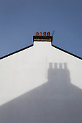 The shadow of a neighbour's chimney on the side of an end-of-terrace house in south London, on 29th January 2019, in Herne Hill, Lambeth, London, England.