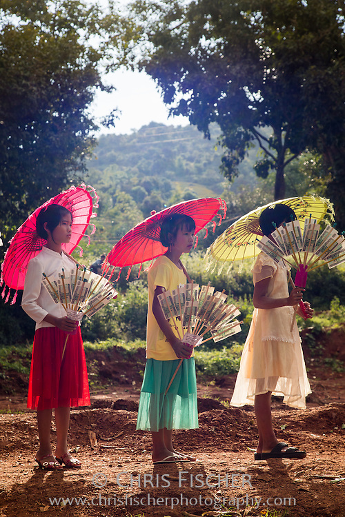 "Young girls awaiting the start of a procession of devotees taking offerings to a local monastery near Pindaya for the Tazaungdaing Festival, held once a year on the full moon in late October/early November. The girls are holding ""money trees"" (""Ngwe-Badei-thabin"") made of crisp bank notes."