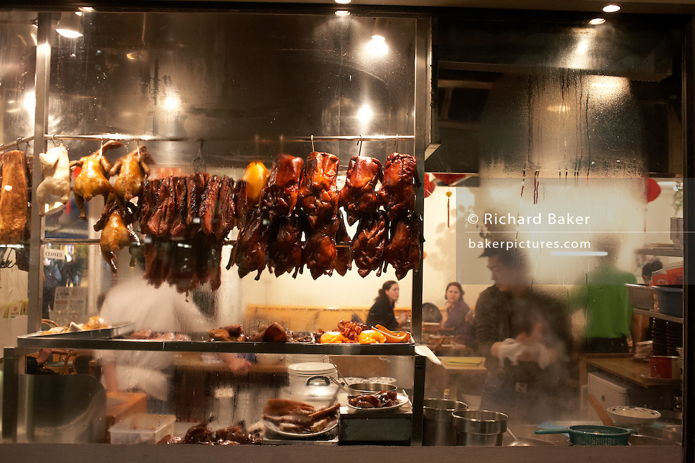 Peering through the steamy window of a Chinese restaurant in London's Chinatown district, we see the shapes and forms of kitchen staff and customers in this lively scene. In the window are rows of Peking Duck with their skins cooked a crispy dark brown. Meanwhile, surrounded by cooking utensils and implements, the tools of their trade, two chefs busy themselves in the kitchen area, one's face shows him to be ethnic Chinese who is rubbing his hands in a cloth before continuing his chores. Two European girls are waiting expectantly for their dishes to arrive. Obscured by the steam and heat, a waiter in green bustles about this small eaterie.