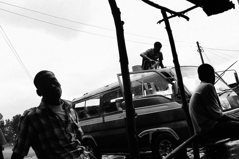 "NAIROBI, KENYA - AUGUST 17, 2011: Members of Carrribean Youth Reform wash Matatus off the main road into Kibera. Formerly called Caribbean Youth Group, the organization changed its name to Caribbean Youth Reform after several violent youth in the neighborhood came under their ranks and were ""reformed"" under their leadership. Begun in 2008 as a result of the post-election violence, the group of youth operate with the goal of uniting the young people of differing tribes. With over 60 members, the group operates a car and carpet washing business as well as manages a weekly garbage collection project through which they clean up neighborhoods, gather manure for compost and sort plastics to sell for income. The group plans to soon build a community toilet and bathroom in the area where the work, and they are also organizing a conflict management and peacekeeping team. Income generated from their activities is consistent but minimal, says acting secretary Abdallah Juma, age 23. Juma says financial instability is the group's primary hurdle to progress. ""We are the founders of this country,"" he said. ""Even without government intervention, we as youth can do it ourselves."" The long term goal of the youth group is to see fewer youth unemployed.<br />
