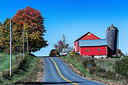 Country road and red barn, Oneida County, New York, USA.