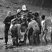 """Steve Christiansen (L) gets a little help from local villagers draining his exhaust pipe of water after crossing the Senphen tributary of the Bangphai River, outside the """"bomb village"""" of Ban Senphen. The village is located in the Ban Phanhop valley, one of the """"chokes"""", or narrow corridors along the Ho Chi Minh Trail in Laos that were heavily bombed by American forces during the Vietnam War. ...."""