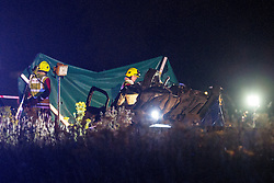 © Licensed to London News Pictures . 21/07/2014 . Nottinghamshire , UK . An overturned car and, behind, a tarpaulin has been erected , as fire crew look on . Police , fire crew and ambulances on the A1 road in Ranby yesterday morning (21st July 2014) following a fatal multi vehicle accident . Leroy and Sheila Carrington (aged 68 and 58) died at the scene when the Peugot 206 they were driving collided with a Vauxhall Astra . Roderick Franks (58) , who was a passenger in the Astra , died in hospital , following the crash . The road was closed in both directions whilst police investigated the scene .  Photo credit : Joel Goodman/LNP
