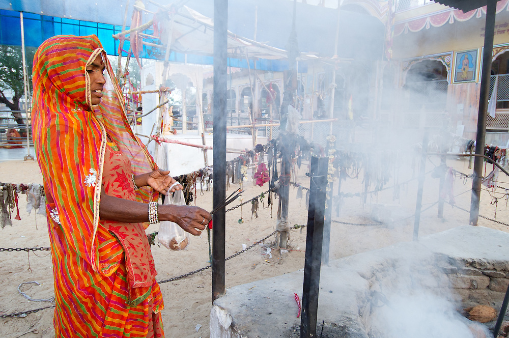 Woman from Rajasthan performing a prayer (puja) using incense, Rajasthan, India.