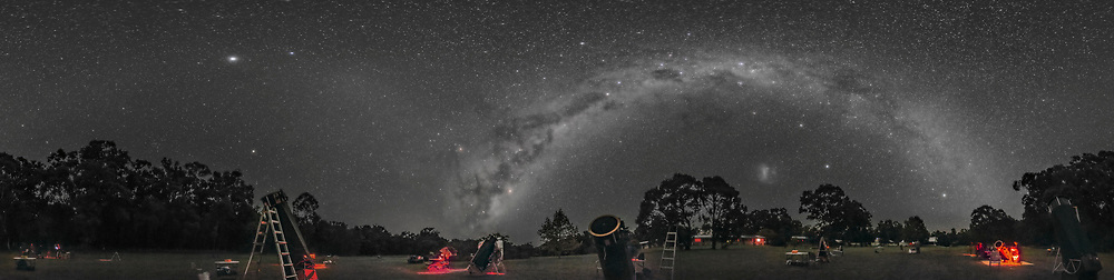 A 360&deg; panorama of the southern hemisphere autumn sky over the observing field at the 2017 OzSky Star Party, at the Warrumbungles Mountain Motel, near Coonabarabran, NSW, Australia. The entire southern Milky Way arches overhead, from Scorpius and Sagittarius rising at left, to Carina and Crux high in the south at centre, to Canis Major and Puppis setting at right. <br /> <br /> The Large Magellanic Cloud is at right of centre. The formation of the Dark Emu in dark dust lanes in the Milky Way is at centre, rising. Some red bands of airglow discolour the sky. <br /> <br /> Jupiter is the bright object at left, with the Gegenschein glow at the anti-solar point between Jupiter and the Milky Way. The faint Zodiacal Band can be seen arching across the sky at left, in the northern sky. The Milky Way dominates the southern sky. The South Celestial Pole is above the tree at right of centre. <br /> <br /> The telescopes on the field are mostly large Dobsonian reflectors in the 18- to 30-inch class, for use of the star party participants. <br /> <br /> This is a stitch of 8 segments, each 30 seconds at f/2.5 with the Rokinon 14mm lens, in portrait orientation, and with the Canon 6D at ISO 6400. Stitched with PTGui in equirectangular projection. This version of the image has been processed to make the view better resemble what you see with the unaided eye, in a largely monochrome and softer view than the colourful and high-contrast views commonly presented in astrophotos. Even at that there is more fine structure present in the Milky Way than the unaided eye usually sees, though binoculars beging to reveal that smaller detail. I have left some colours in some stars and in the foreground of landscape scenes.